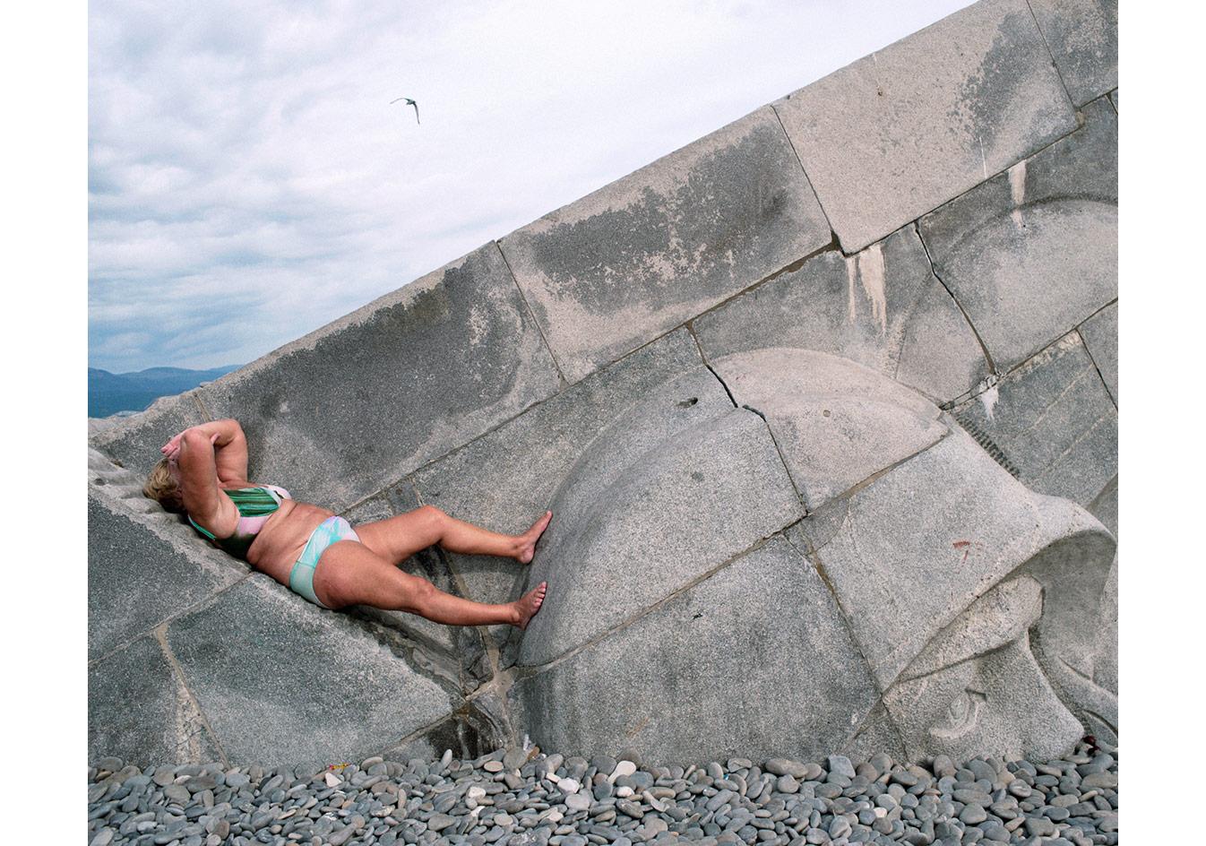 Novorossisk'teki devasa anıtın üzerinde güneşlenen bir kadın, Rusya © Mathias Depardon