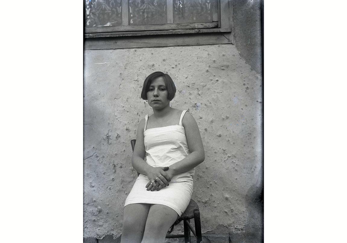 Askılı, mini etekli elbiseli kadın, duvar önünde oturmuş, 1920'ler-30'lar