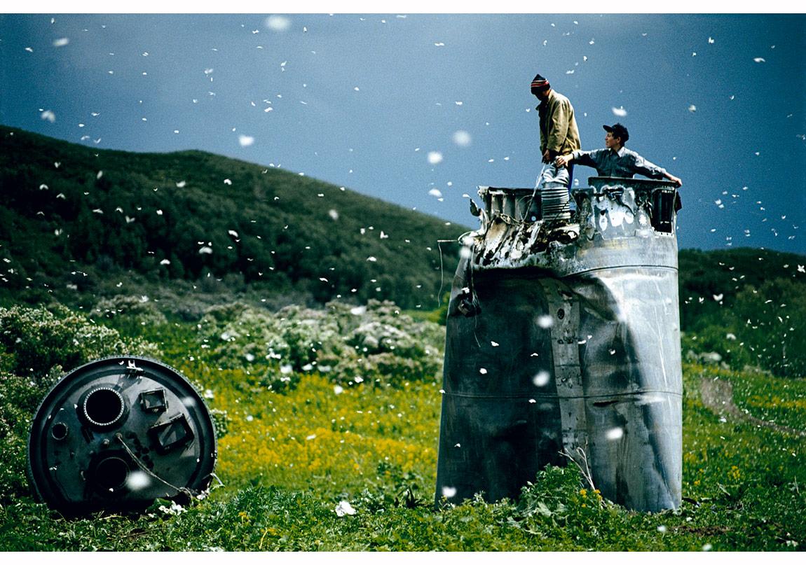 © Jonas Bendiksen/Magnum Photos,Altay Bölgesi, Rusya, 2000. Binlerce beyaz kelebek arasında, parçalanmış bir uzay aracından hurda toplayan köylüler. Çevreciler zehirli roket yakıtları yüzünden bölgenin geleceğinden endişe ediyor.