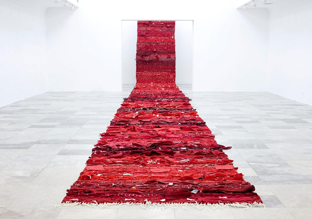Kırmızı HalıŠejla KamerićKırmızı Halı, (M) ve (L), 2012İkinci el kıyafetlerden örülmüş el yapımı halı1640 x 140 cmYerleştirme görüntüsü: Kosova Ulusal Galerisi, Priştine, 2015Sanatçının izniyleFotoğraf: Jetmir İdrizi