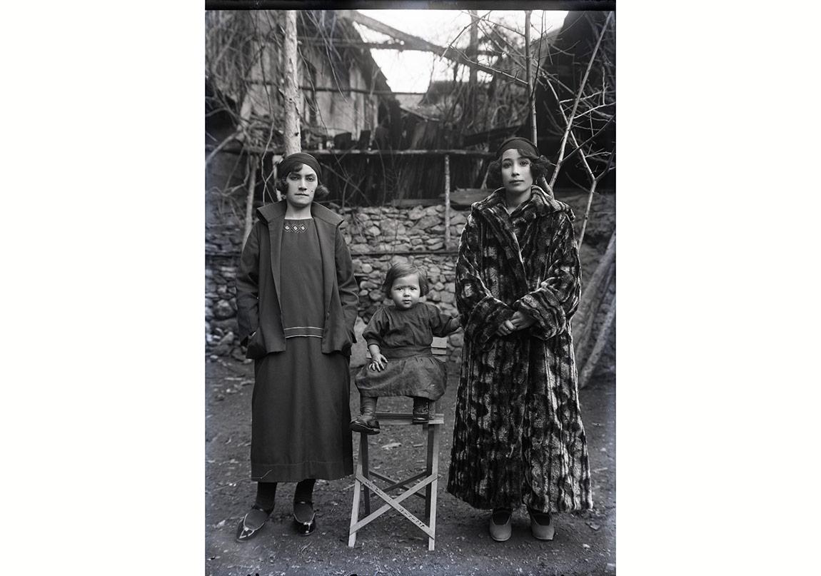 Saçları yapılmış, biri kürk paltosu ile dikkat çeken iki kadın, ortalarında sandalyeye oturtulmuş çocuk, 13 Ocak 1926