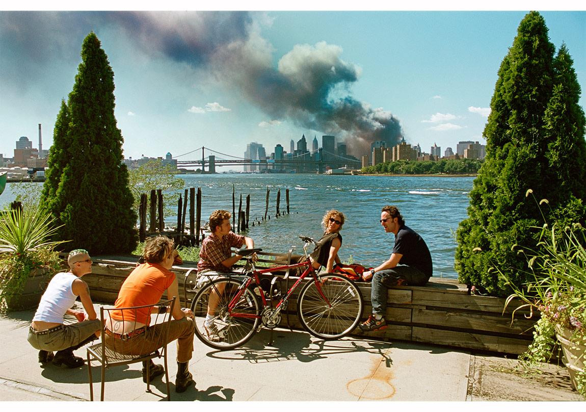 © Thomas Hoepker/Magnum Photos,11 Eylül 2001, Brooklyn, New York, ABD. New York'ta Manhattan'ın aşağı bölgesinde bulunan Dünya Ticaret Merkezi, düzenlenen saldırı sonrasında yükselen duman bulutlarıyla kaplanmışken, Brooklyn'de bu manzarayı gören bir noktada öğlen yemeği molası sırasında sohbet eden gençler.