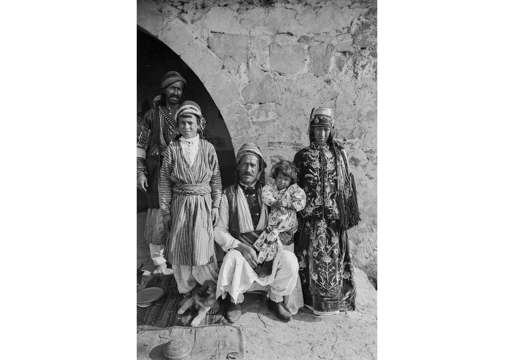 Garstang ve ekibi Kilis, Karakıl köyünden geçerken kamerasına poz veren bir Kürt ailenin sekiz resimlik serisinden biri (1907). Garstang Arkeoloji Müzesi, Liverpool Üniversitesi.HIT-K-001